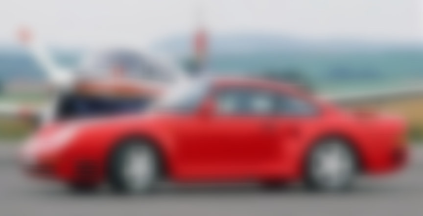 Red Porsche 959 in front of an airplane